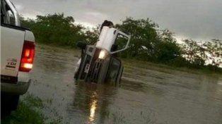 Una persona alcanza de salir de la camioneta que quedó atrapada con el agua.