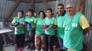 La producción artesanal la realizan trabajadoras y un maestro del oficio, aquí junto al presidente comunal.