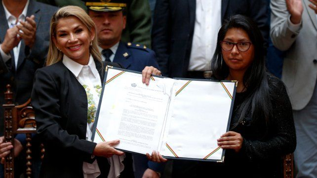 Paso clave. La presidenta Añez exhibe el texto aprobado junto a la titular del Senado