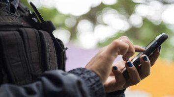 Atenta a la pantalla. Una mujer de la fuerza mira su teléfono móvil en plena actividad de custodia.