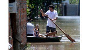 Inundados. Los vecinos la Vuelta del Paraguayo se trasladan y cargan sus pertenencias en los botes. Algunos se niegan a dejar el lugar