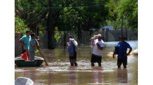 Los vecinos salen caminando de sus casas con el agua a la altura de las rodillas.