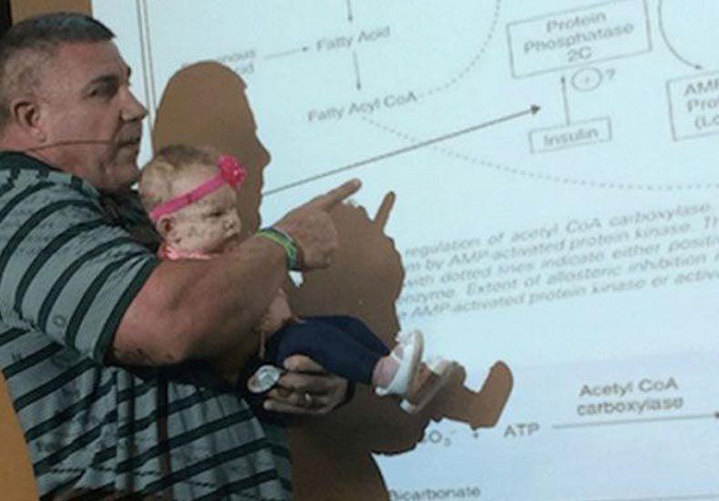 Un profesor da la clase con la bebé de una alumna en brazos