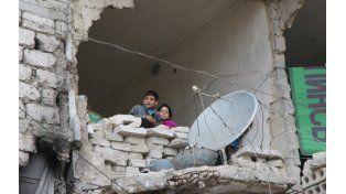 El Drama de la guerra. Niños observan desde una de los miles de viviendas destruidas por las bombas en Alepo.