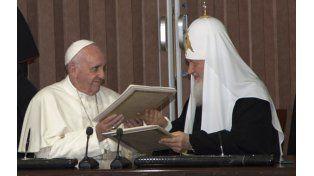 Confraternidad. El Papa y el patriarca Kirill intercambian ejemplares del acuerdo para firmarlos.