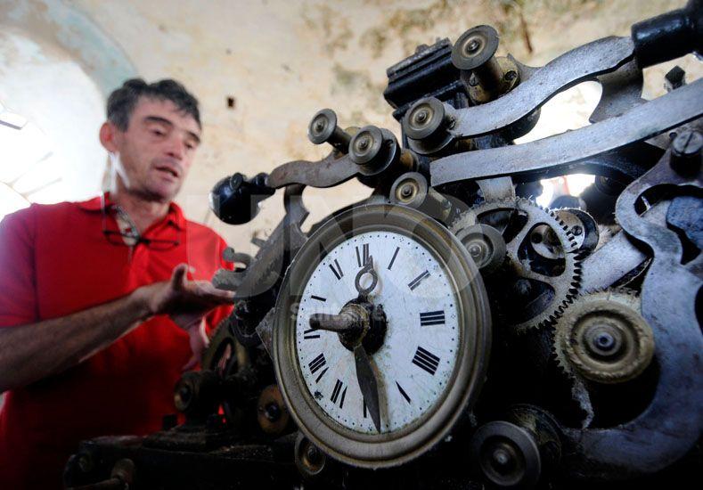 Limpieza. Un operario de la empresa lleva adelante la refacción del antiguo reloj de la parroquia.