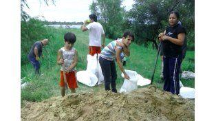 Protección. Los vecinos de Colastiné Sur arman bolsas con arena y tierra para colocar en las defensas.