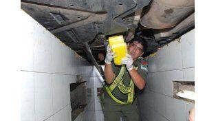 Un gendarme retira los paquetes con droga del chasis de un auto Mercedes Benz que viajaba a Santa Fe. (Gentileza Clorinda Noticias)