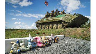 Homenaje. Militares de la autoproclamada República Popular de Donetsk pasan frente al sitio donde cayó el Boeing.