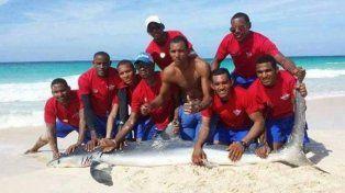Un tiburón agonizó hasta la muerte mientras unos socorristas posan con él para una foto