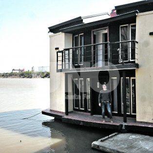 Dique II. El arquitecto Jorge Rico junto a la casa que se encuentra amarrada a escasas cuadras del centro de la ciudad.