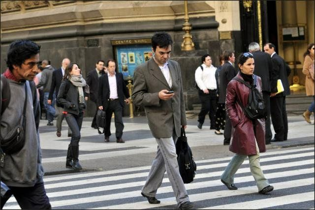 Podrían sancionar a los peatones que crucen la calle mirando el celular