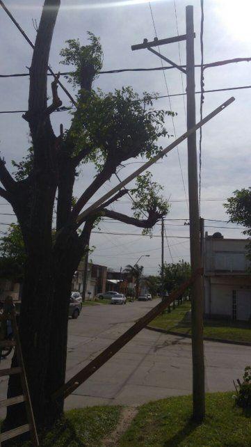 Vecinos sostienen un poste de luz con una escalera y palos para que no se caiga