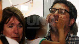 Sergio Gigliotti y Cristina Morla. Kiki en los brazos de él, minutos antes de despedirse del niño, en la secretaría de Niñez.