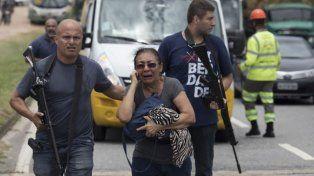 Operativos policiales. Fuerzas policiales con armas largas protegen a una mujer tras un violento tiroteo en Río de Janeiro. Foto: AP