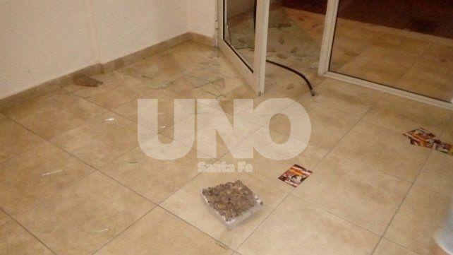 La baldosa con la que el delincuente rompió el vidrio de la puerta del edificio