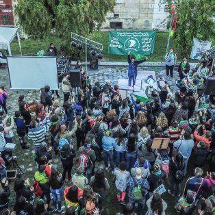 Norma Cuevas en el escenario hablando frente a la multitud mientras sostiene en alto el pañuelo verde de la Campaña por el Aborto Legal, Seguro y Gratuito