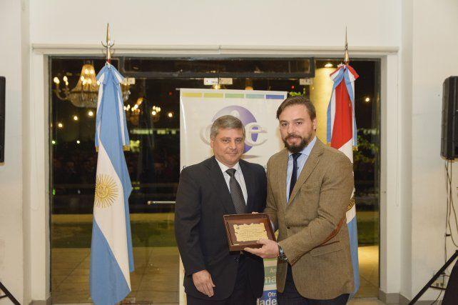 El Dr. Juan Pablo Gutiérrez recibe la placa homenaje de manos del Ing. Raúl Bustaber