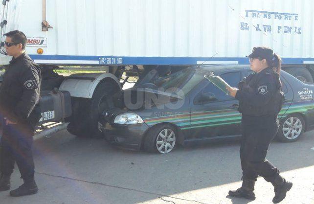 El auto oficial quedó bajo una camión.