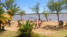 Turistas de jeans y camisa caminando por la playa del balneario Municipal de Paraná. Foto UNO.